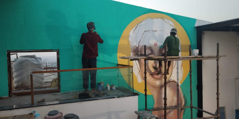 Aftab painting a mural in Noida
