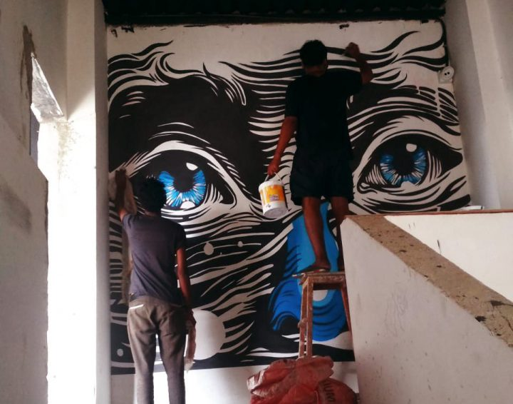 Aftab painting a mural with Inderjeet