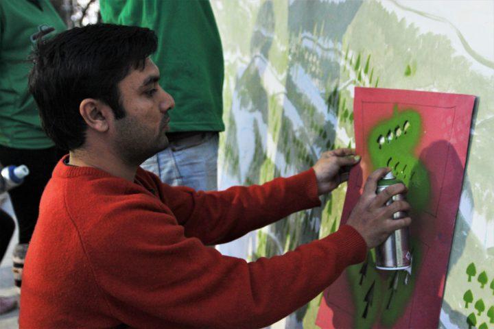 Zain paints a waste mural in Dharamshala